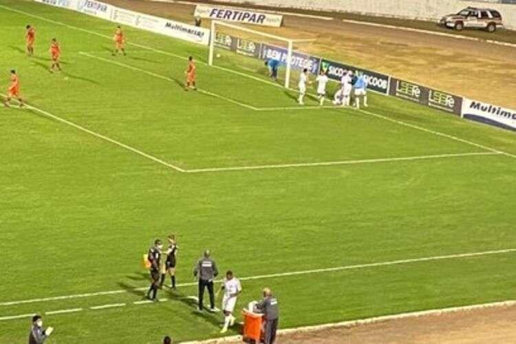 Estádio de futebol com jogadores em campo e pessoas por trásDescrição gerada automaticamente