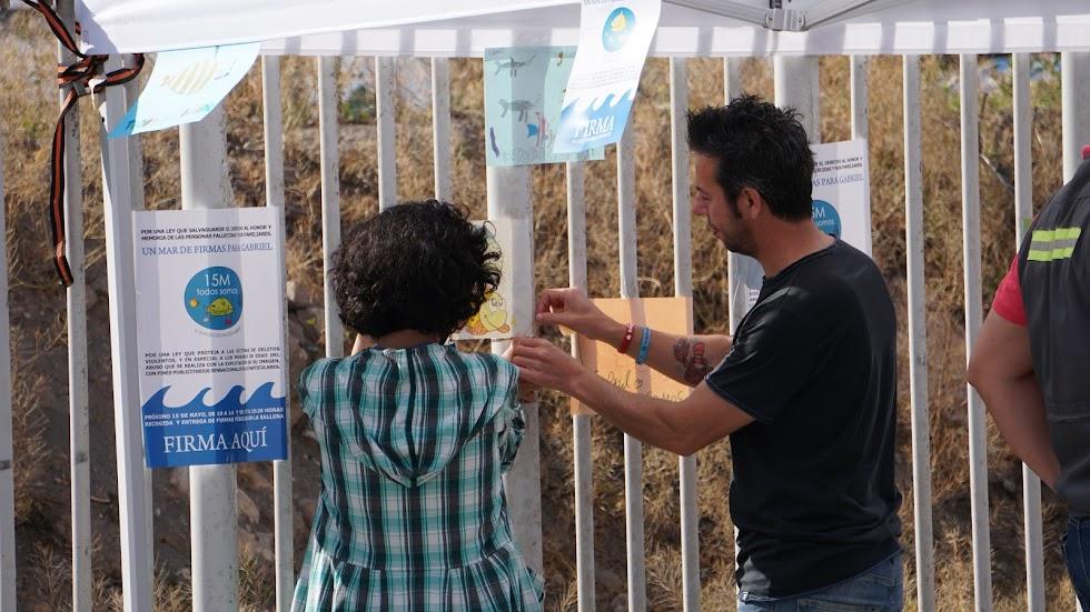 Patricia y Ángel colocando uno de los dibujos dedicados a Gabriel