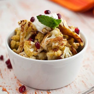 Cumin Seed Roasted Cauliflower with Salted Yogurt, Mint, and Pomegranate Seeds.