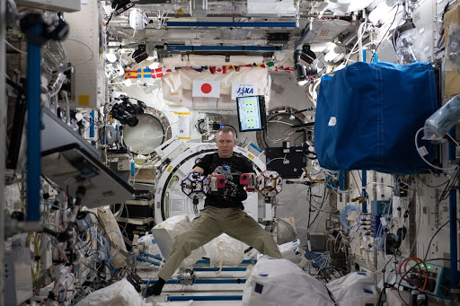 Expedition 55 Flight Engineer Drew Feustel works inside the Japanese Kibo laboratory module with tiny internal satellites.