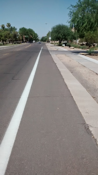 Photo: Knox Rd east of Rural. This is a designated bike lane. Most streets with sidewalks have a curb and the sidewalk is raised a few inches. This collector street has sidewalks but they're flush with the roadway, and there's no curb, just a kind of flat gutter pan. One imagines curbs are often necessary to direct stormwater drainage.