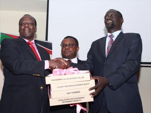 Newly elected Council of Governors chairman Kakamega governor Wycliffe Oparanya is congratulated by Turkana governor Josphat Nanok on Monday, January 14, 2019 as Senate speaker Kenneth Lusaka looks on. /EZEKIEL AMINGA