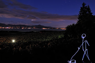 Photo: LX357  Shot from a vineyard of the village of Aubonne (Switzerland).  The light ray in the sky shows the move of a plane. I checked on the internet, it should be a plane from London, flight LX357.. that is why I gave this name to the light painting. In the background, the Alps are visible.  I may try to realize a HDR version of this photo using Trey Ratcliff tutorial as it is pretty dark where the light character stands.  New light painting to be published soon ^^