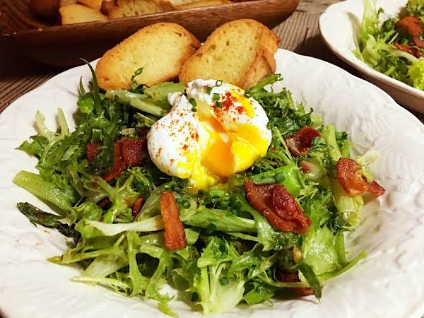A Salad With Pieces Of Bacon And Topped With A Poached Egg With Two Crostini Behind.