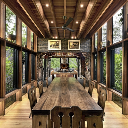 A wood and glass 'bridge' connects the lounge and kitchen and houses the dining area – the floor-to-ceiling windows again connecting the structure to the landscape.