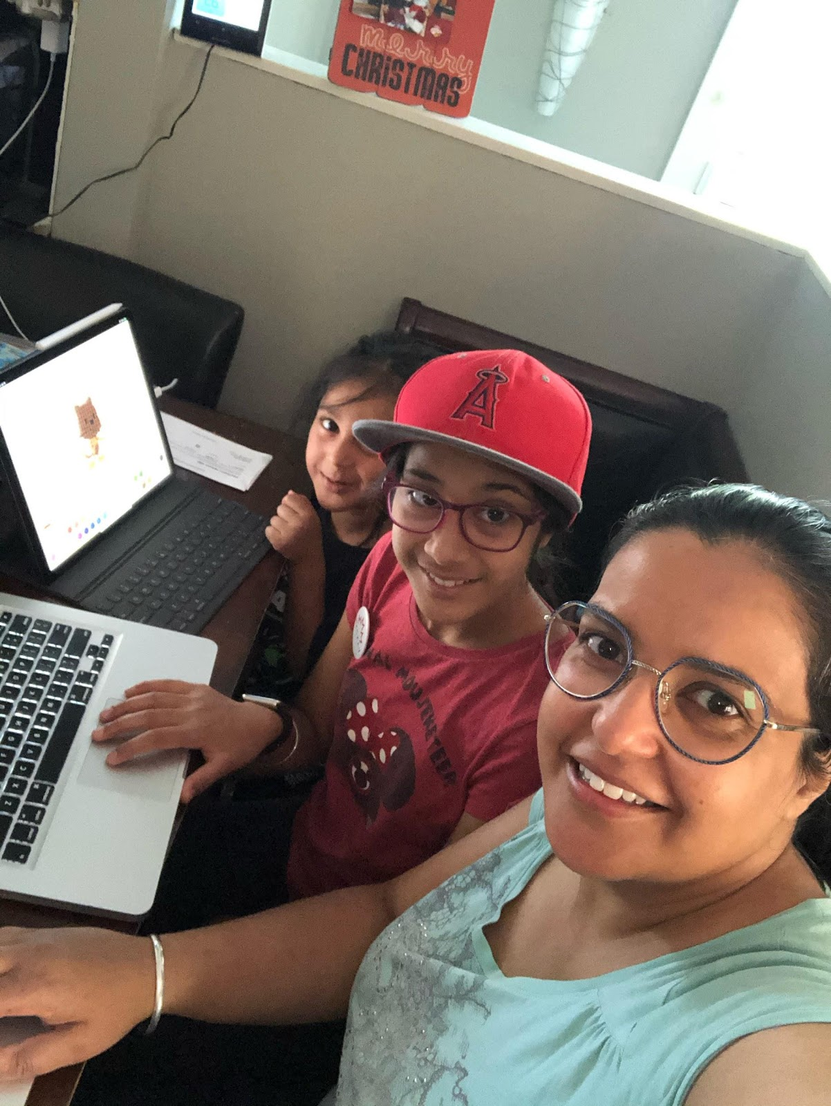 Mom and two her daughters sitting in front of their laptops and smiling to the camera