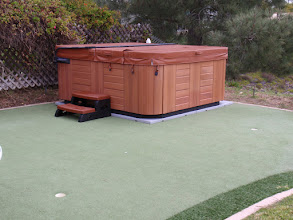 """Photo: We've wanted a hot tub for years but were not sure where we could put it. The previous owners installed a putting green in the back yard, and while we are not golfers, we did not like the idea of potentially ruining the surface by placing a heavy hot tub on it which would most likely damage it after a few years.  The EZ Pad was a great solution! Not only does it protect the """"green"""" underneath, we were able to place the hot tub (which is square) into the corner of the putting green (which is round) and maximize available area for usage. EZ Pad also was a perfect fit for the hot tub we bought, whose dimensions are """"larger"""" than the 8' x 8' pad; it still fits because the actual foot print the hot tub is less than 8' x 8'. Perfect match!  Carl S, San Diego, CA"""
