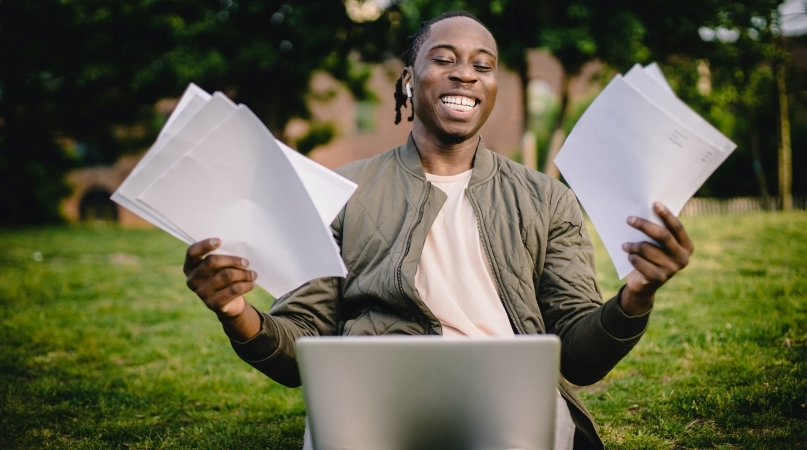 man smiles while holding multiple moving cost estimates