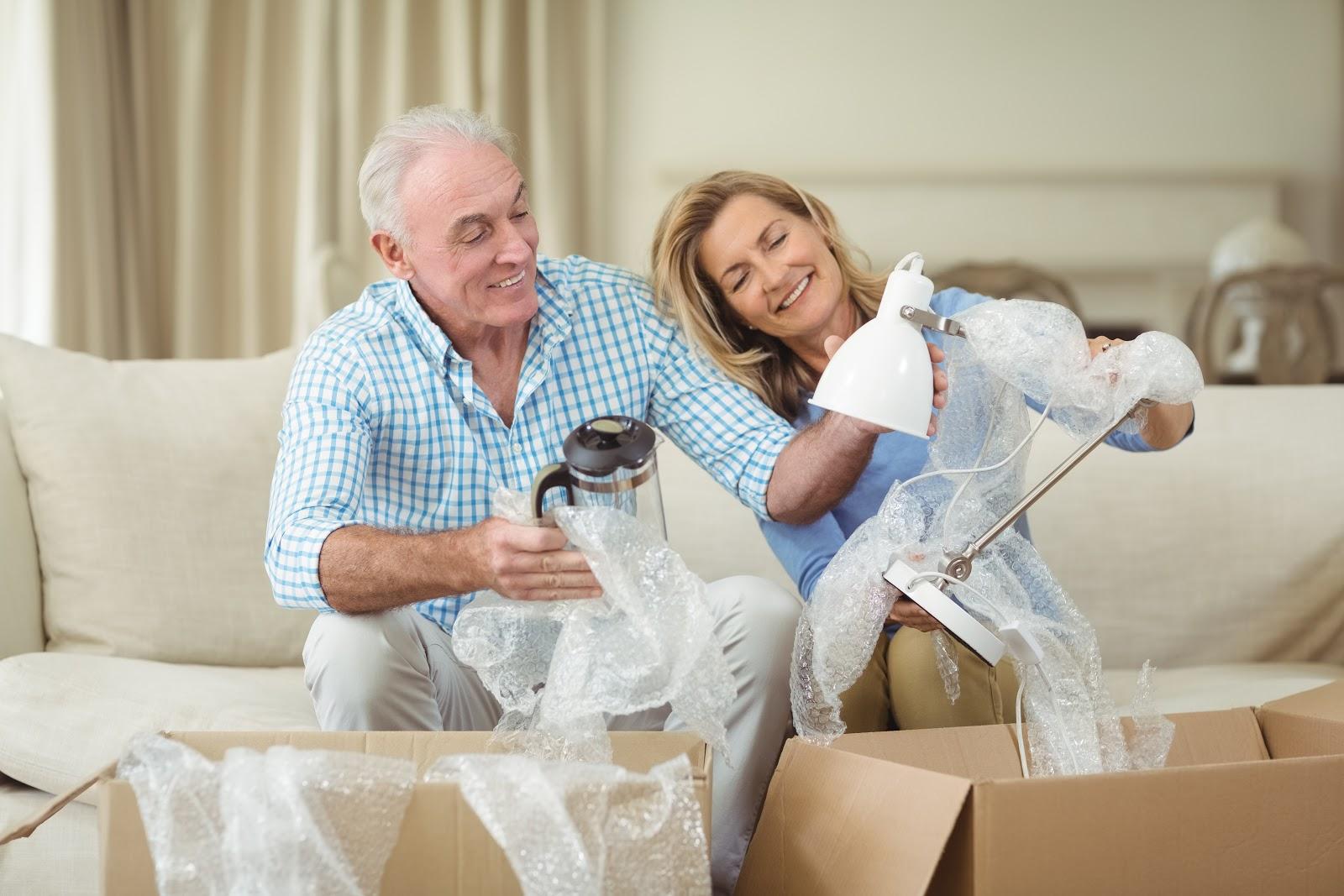 Um casal desempacotando peças em uma mudança residencial.
