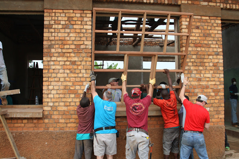Photo: Be The Change Volunteer team from Columbia are helping local students in Rwanda putting in new windows in their classroom, which was destroyed during the genocide.