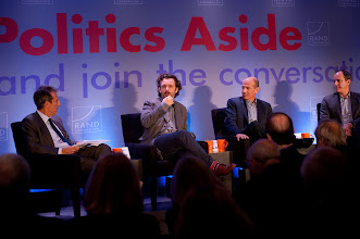 """Photo: Michael Sheen responds as Moderator Michael Lynton (left) and panelists Howard Gordon and David Nevins look on during the """"Hollywood and Policy"""" panel discussion Friday, Nov. 16 at the RAND Politics Aside event in Santa Monica."""