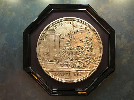 oosterdam-stairwell-art.jpg - Guests on ms Oosterdam can see art in the stairwells such as this replica of a historic coin showing seafarers battling rough waters in a masted ship.