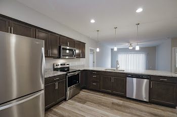 Bella Grand floorplan kitchen with stainless steel appliances and dark cabinets