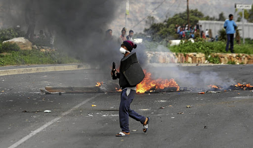 ON THE PROWL: A protester has a petrol bomb at the ready during clashes with riot police in Hout Bay.