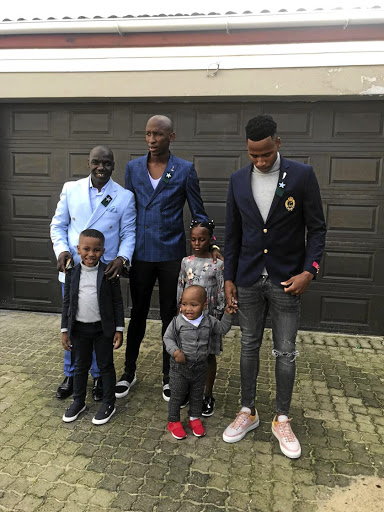 Mark Mayambela, centre, at home with relatives.