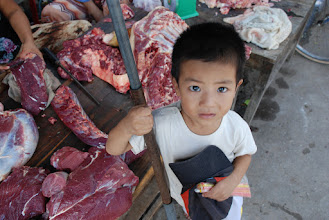 Photo: A kid accompanying his mom to the market and was fascinated by the lens.