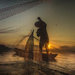 fisherman by Visoot Uthairam - People Portraits of Men ( water, countryside, orange, reflection, fish, thailand, boat, net, rural, sun, country, asian, life, color, fresh, sunset, shadow, asia, sunshine, sunrise, fishing, fisherman, light, black, river )