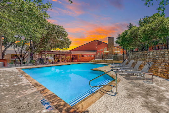 Silverton's refreshing swimming pool with trees surrounding and lounge chairs at dusk