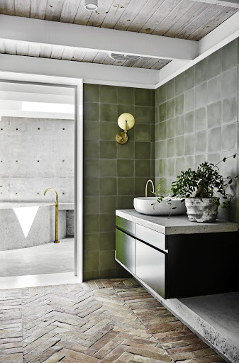 Olive green tiles and cabinetry were teamed with aged brass tapware and a concrete benchtop to give the original bathroom a modern makeover.