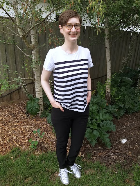 Siobhan stands in front of a garden fence. She wears slim fit black pants with hard-to-notice front pockets, striped white and navy short sleeve tee and silver runners. Her hands are in the pant pockets.
