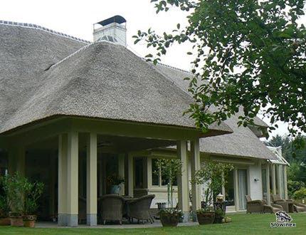 Elegancka willa z gankiem na filarach z dachem pokrytym szarą trzciną