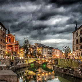 Clouds over Ljubljana by Andreja Svenšek - City,  Street & Park  Historic Districts ( clouds, building, art, ljubljana, travel, quiet, cityscape, storm, historic, city, arhitecture, slovenia, cloud, bridge, historical, light, travel photography, sightseeing, river,  )