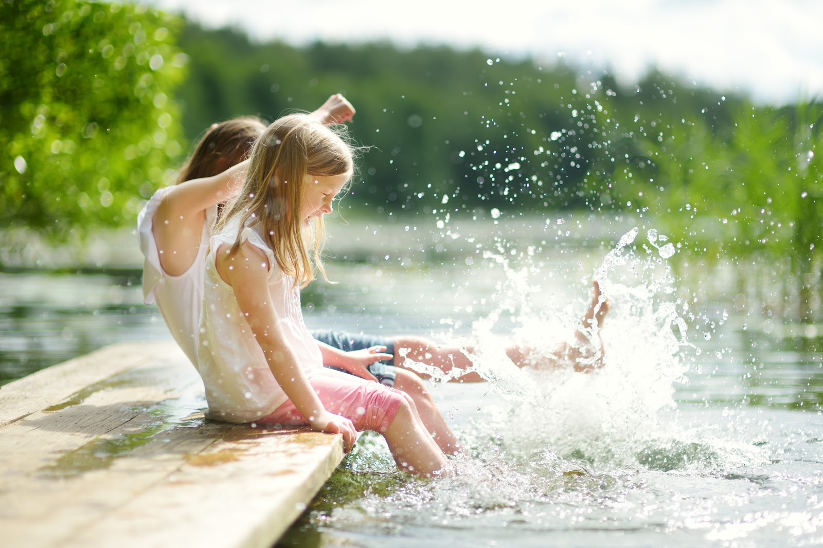 Young girls splashing in the water on a lake dock