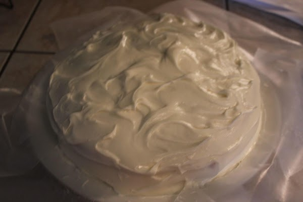 Once cake is cooled, carefully spread 1/2 the frosting over the bottom layer. ...