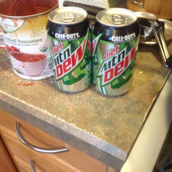 Then add in the undrained sliced mushrooms, both cans of Mountain Dew soda, basil...