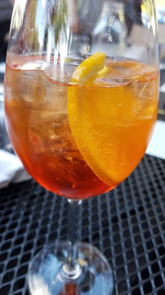 Aperol Spritz with Aperol, Sparkling Wine, and orange wheel, one of six curated cocktails offered at Ken's Artisan Pizza