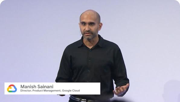 Man in dark shirt on stage gestures and speaks