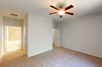 Bedroom with plush carpet, ceiling fan, and neutral colored walls