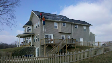 Photo: Roofers were out before noon the morning after the storm to begin patching the roof.
