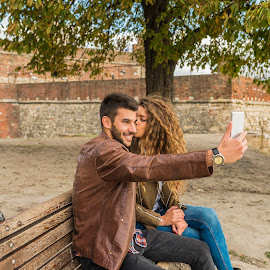 Selfie in the public park. by Vera Arsic - People Couples ( young women, romance, two people, friendship, heterosexual couple, togetherness, young adult, social networking, river bank, selfie, model, connection, communication, smiling, attractive, bench, smart phone, telephone, lovers, lifestyles, girlfriend, enjoyment, color image, adult, photography, city, boyfriend, affectionate, modern, romantic, happiness, joy, dating, flirting, caucasian ethnicity, wooden bench, public park, nature, carefree, sexy, intimate, young men, technology, people, love emotion, young couple, outdoors, bonding, couple relationship, growth, fun, fashion, laughing )