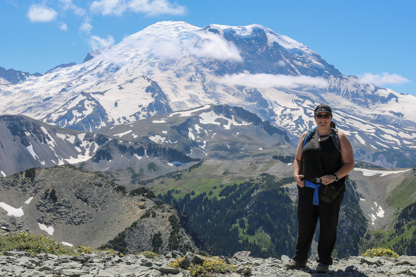 Good boots are key part of how to start hiking.  A female hiker poses on a rocky hill in front of a snow covered Mount Rainier.
