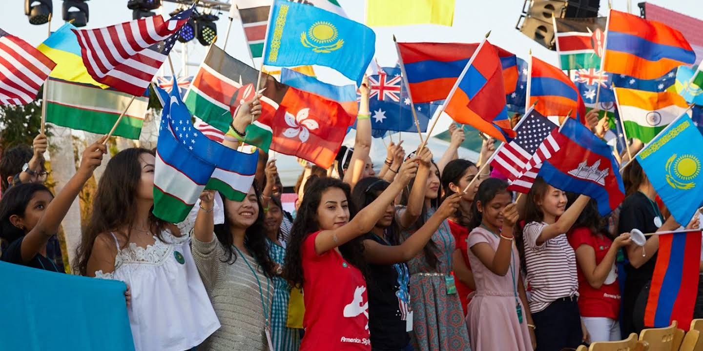 Several girls raising flags according to their nationality