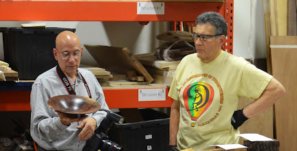 Photo: Clif looks on as Mike shows his flared walnut bowl.