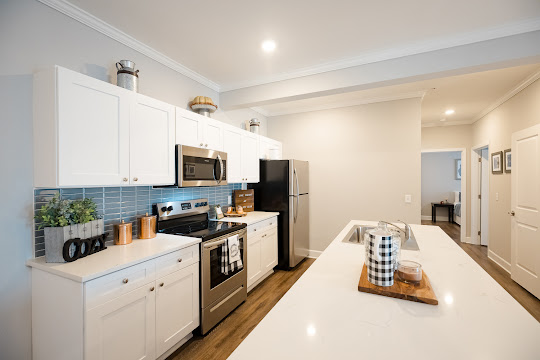 Kitchen with stainless steel appliances, white cabinets, blue tile backsplash, and quartz countertops