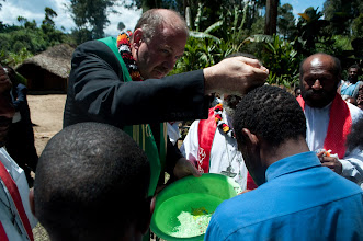 Photo: Rev. John Mehl baptizing a young man in Papua New Guinea.