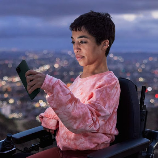 A woman is taking a selfie with her Pixel at night on a hill overlooking a city.