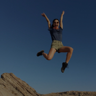 Woman outside, jumping with arms in the air