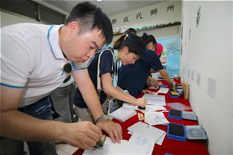 Photo: 參與研習營的同學們在太平島郵政代辦所,興奮地蓋上島上獨家的紀念章,預備將明信片從國之最南境,寄予親朋好友。(軍聞社記者周力行攝)