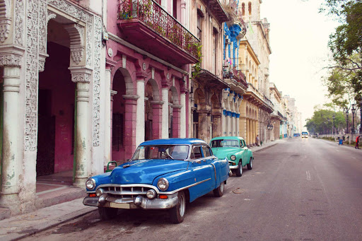 Cuba-Two-Cars-Parked-on-Street-With-Colorful-Buildings2.jpg - Visit Old Havana on a cruise.