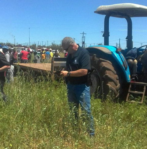 People gathering at the scene where a farm worker was allegedly killed for driving a stolen tractor.