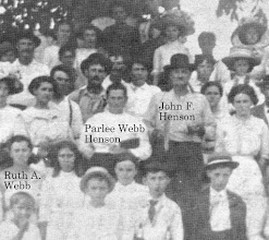 "Photo: Parlee and John F. ""Blackberry""  Henson with family and congregation, probably at Brush Creek RLDS, Wayne County, Illinois. Notice they are holding what appears church-related material. John was an itinerant minister of the RLDS from Wayne County, a few miles north of Johnson County. John and Parlee most likely met in the 1890s when he visited the Tunnel Hill RLDS. After John's death in 1912, Parlee for a brief period lived at Independence, MO, where the RLDS has its headquarters."