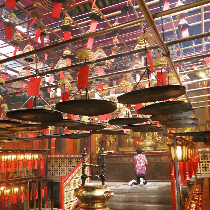 A worshipper prays in the Man Mo Temple.