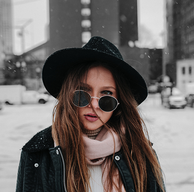 Stock image of woman in hat and sunglasses against blurred snowy city background. Now background is desaturated to black and white.