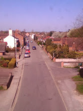 Photo: Residential housing heading north up Prospect St. at Horncastle, but on the right far distance by the first driven car, the bollards and red bin mark the pedestrian cut thru to Tesco. Elmhirst Lakes cabins are at the top of this road.