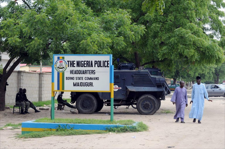 People walk past police armoured tank stationed at the main gate of the state police command headquaters in Maiduguri, Borno State Monday on July 26, 2010.