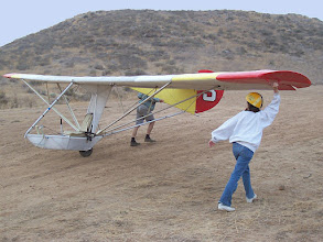 "Photo: Goat3 gets walked up the hill for another training flight, November 2006. Novice training is not easy for the student pilot. There's a lot going on, with all three controls needed from the very beginning, the need to steer while rolling, and having to balance on a single wheel. The basic training formula is: ""nose level, wings level, steer with your feet""."